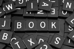 La lettre noire couvre de tuiles orthographier le mot et le x22 ; book& x22 ; Photos libres de droits