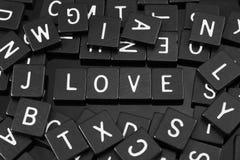 La lettre noire couvre de tuiles orthographier le mot et le x22 ; love& x22 ; Image stock
