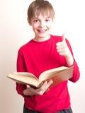 La lettura è divertimento - il ragazzo teenager dà i pollici in su Immagine Stock Libera da Diritti