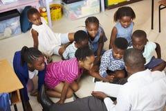 La lettura dell'insegnante scherza un libro in una lezione della scuola elementare Fotografia Stock Libera da Diritti