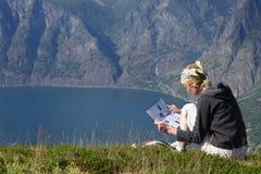 La lettura di seduta della donna mappa nelle montagne sopra il lago Fotografia Stock Libera da Diritti