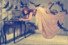 La levitazione ha sparato di una donna e dei suoi uccelli neri Fotografie Stock Libere da Diritti