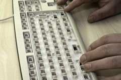 La libertà di parola, la censura ed i divieti di Internet, un uomo lavora ad una tastiera senza chiavi fotografia stock
