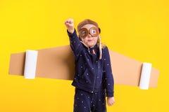 La libertà, ragazza che gioca per essere pilota dell'aeroplano, bambina divertente con il cappuccio dell'aviatore e vetri, porta  Fotografia Stock