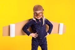 La libertà, ragazza che gioca per essere pilota dell'aeroplano, bambina divertente con il cappuccio dell'aviatore e vetri, porta  Fotografia Stock Libera da Diritti