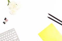 La libreta amarilla, el teclado de ordenador, los clips de papel, el lápiz negro dos y un crisantemo florecen en un fondo blanco  Fotos de archivo