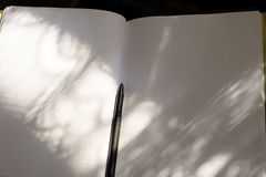 Cuaderno blanco y pluma negra en la luz del sol Foto de archivo