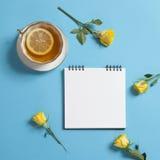 La libreta cuadrada el las primaveras con el papel de Kraft blanco, la rosa del amarillo y la taza de té están en un fondo azul Foto de archivo