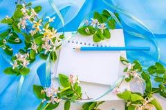 La libreta en blanco, se corrige y las flores Imagen de archivo