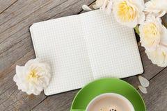 La libreta, la taza de café y la rosa en blanco del blanco florece Imagenes de archivo