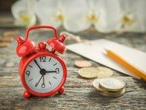 La libreta roja del despertador para escribir a lápiz el dinero euro acuña en la tabla rústica de madera Fotografía de archivo libre de regalías