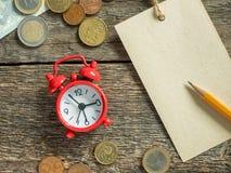 La libreta roja del despertador para escribir a lápiz el dinero euro acuña en la tabla rústica de madera Imágenes de archivo libres de regalías
