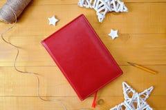 La libreta roja del fondo de la Navidad para su texto y la Navidad blanca protagonizan un fondo de madera Endecha plana, foto de  Imagen de archivo libre de regalías