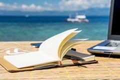 La libreta vacía abierta está en la tabla con el teléfono y los auriculares en el fondo tropical del mar Imagen de archivo libre de regalías