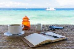 La libreta vacía abierta está en la tabla con la taza de café, de teléfono y de auriculares en el fondo tropical del mar Imágenes de archivo libres de regalías