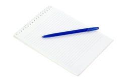 La libreta y mentira en una pluma azul aislada en blanco Fotos de archivo