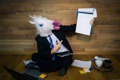 La licorne dans un costume et un lien sourit et montre une feuille vide blanche avec l'espace de copie Image libre de droits