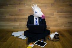 La licorne sérieuse dans un costume et un lien travaille avec enthousiasme à la maison le bureau Photo libre de droits