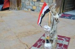 La liebre gris se coloca en la manta que sostiene la bandera egipcia en sus patas y que fuma una cachimba, un espantapájaros fotografía de archivo