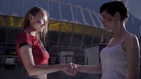 La liga de los campeones, dos fanáticos del fútbol de las chicas jóvenes en la lluvia está sacudiendo las manos, fps del concepto almacen de metraje de vídeo