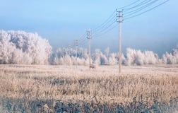 La ligne électrique dans la neige a couvert le champ photographie stock