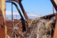 La ligne électrique et la neige couvrent la fenêtre de voiture rouillée de cuvette vue par montagnes avec le foin élevant le vieu Image libre de droits