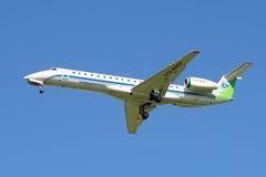 La ligne aérienne à bord Komiaviatrans de l'avion VQ-BWU d'Embraer ERJ-145LR dans le ciel bleu Images libres de droits