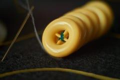 La ligne de l'habillement jaune se boutonne, aiguille avec le fil sur l'unité centrale d'aiguille Photos stock