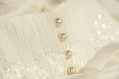 La ligne de la perle se boutonne sur une robe de mariage Photographie stock libre de droits