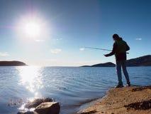 La ligne de pêche de contrôle de pêcheur et poussée de l'amorce sur la tige, se préparent et jettent l'attrait loin dans l'eau pa Photo stock
