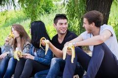 La ligne des amis s'asseyant ensemble mangent la banane images libres de droits