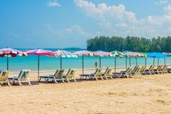 La ligne des parapluies de plage et prennent un bain de soleil des sièges sur la plage de sable de Phuket Photos stock