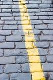 La ligne jaune sur la route reculant la pierre Image stock