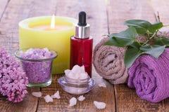 La lila florece, rueda con la sal del mar, vela ardiente, botella roja w Imagenes de archivo