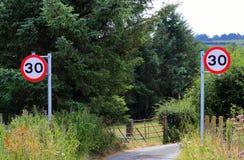 La limitation de vitesse jumelle signe les Anglais au début de la ruelle de pays Images stock