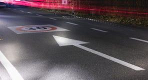 La limitation de vitesse se connectent une route de macadam par nuit Photographie stock libre de droits