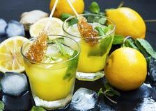 La limonada fresca bebe los vidrios con las hojas de menta, limones, cubos de hielo Foto de archivo libre de regalías