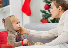 La limpieza de la madre come al bebé manchado que come las galletas Fotografía de archivo