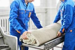 La limpieza de los trabajadores de los hombres consigue la alfombra de una lavadora automática y la lleva en el secador de ropa fotos de archivo