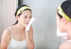 La limpieza de la mujer que se lava la cara con la toalla refleja con el espejo del cuarto de baño Fotografía de archivo libre de regalías