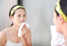 La limpieza de la mujer que se lava la cara con la toalla refleja con el espejo del cuarto de baño Imagenes de archivo