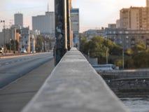 La linea del ponte al lato della città, il tramonto, case sull'orizzonte, la bellezza della città immagini stock