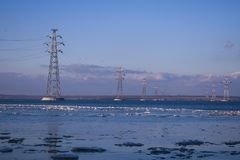 La linea di trasmissione elettrica che passa attraverso il fiume contro fotografie stock