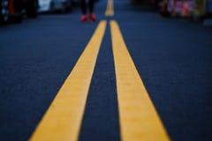 La linea gialla della strada sulla via nera Immagini Stock