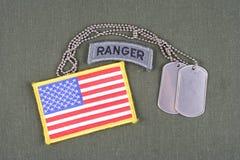 La linguetta del guardia forestale dell'ESERCITO AMERICANO con la toppa della bandiera e della medaglietta per cani su verde verd Fotografia Stock