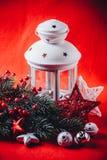 La linterna blanca de la Navidad se está colocando con una vela ardiente en ella con una rama de árbol de abeto y el punto protag Foto de archivo