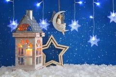 La linterna de madera vieja, copos de nieve platea la luz de la guirnalda, la hada en la luna sobre la nieve y el fondo azul imagen de archivo