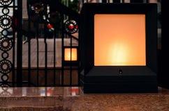 La linterna del negro de la calle del vintage en la losa de mármol cerca forjó enrejado Diseño, luz natural, espacio de la copia foto de archivo libre de regalías