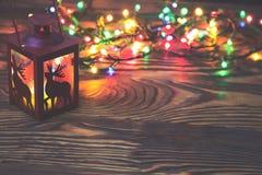 La linterna roja decorativa del metal con un recorte de los ciervos se encendió por una vela que brillaba intensamente con la luz Imagenes de archivo