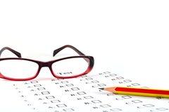 La lista de la prueba y el lápiz y los vidrios Fotos de archivo